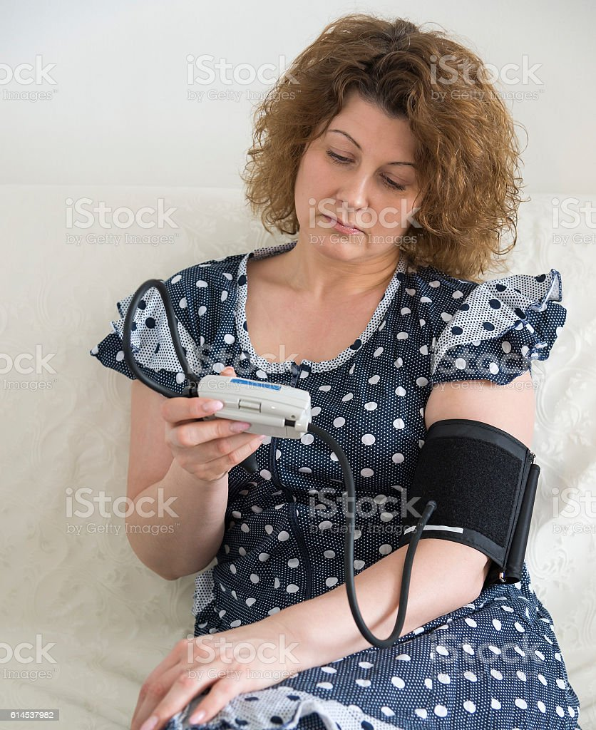 woman in a housecoat measures yourself blood pressure stock photo