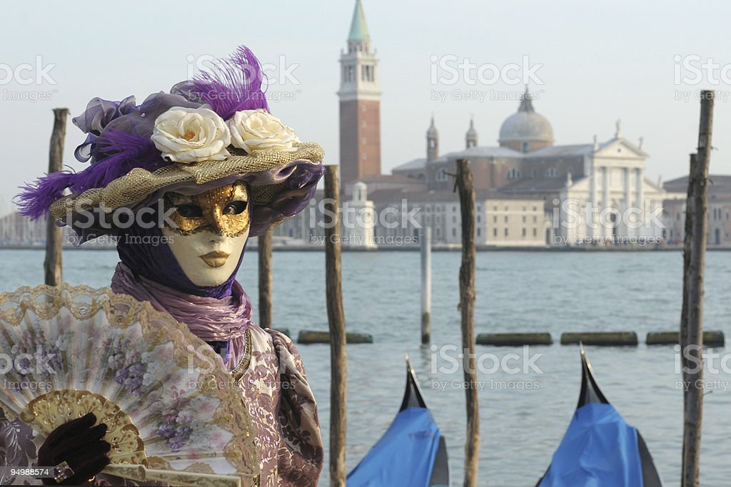 Woman in a mask with a fan at a carnival in Venice stock photo