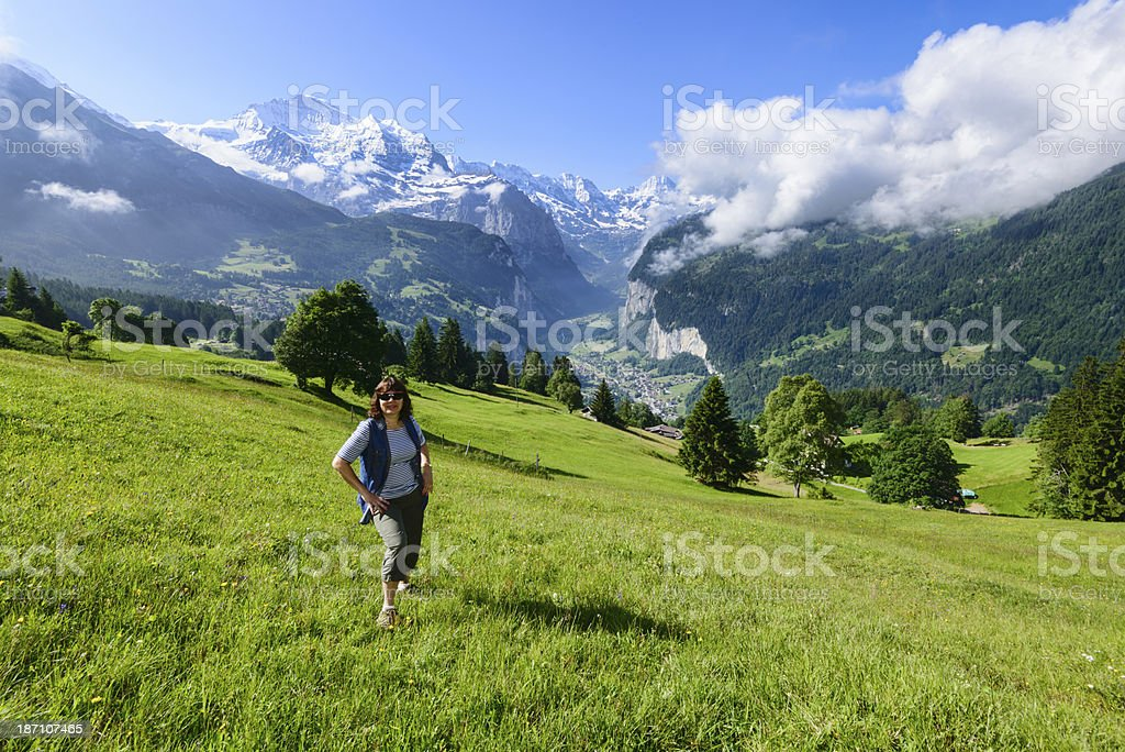 Woman in a meadow with valley and snowcapped mountains -XXXL royalty-free stock photo