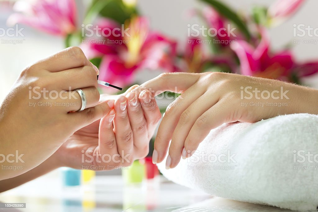 Woman in a nail salon receiving a manicure stock photo