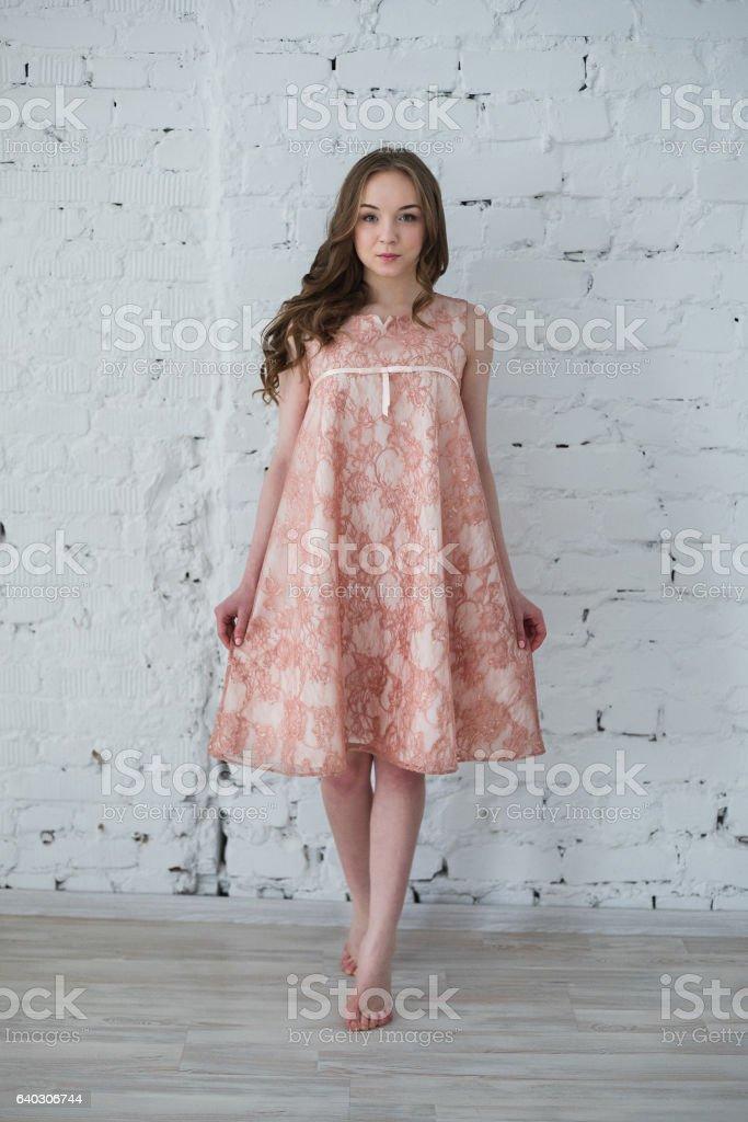 woman in a peach dress against the white brick wall stock photo