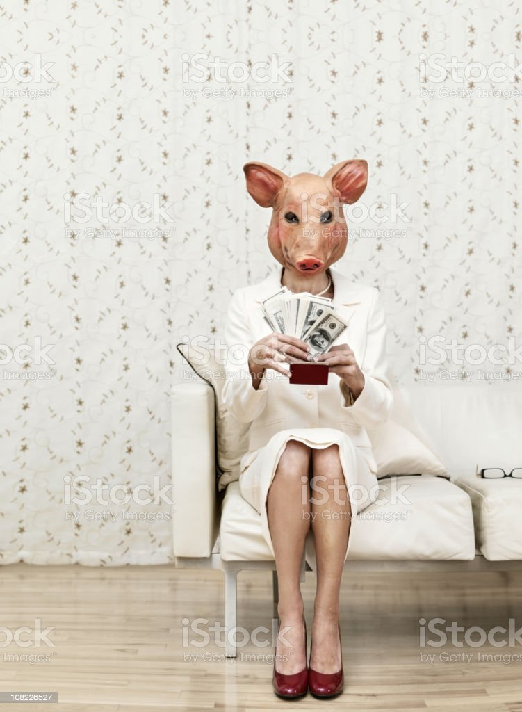 Woman in a pig mask holding cash stock photo