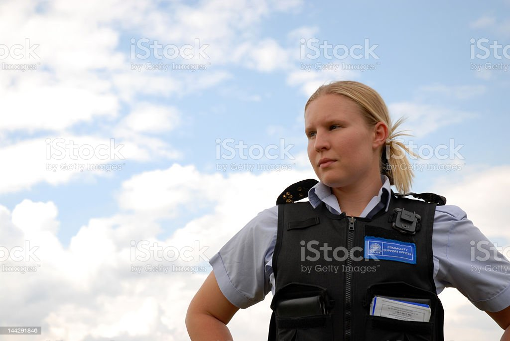 A woman in a police vest standing in front of the sky stock photo