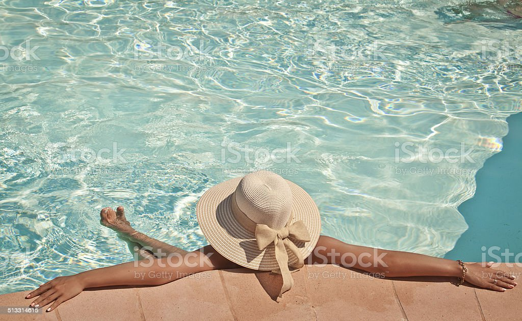 Woman in a pool hat relaxing in a blue pool stock photo