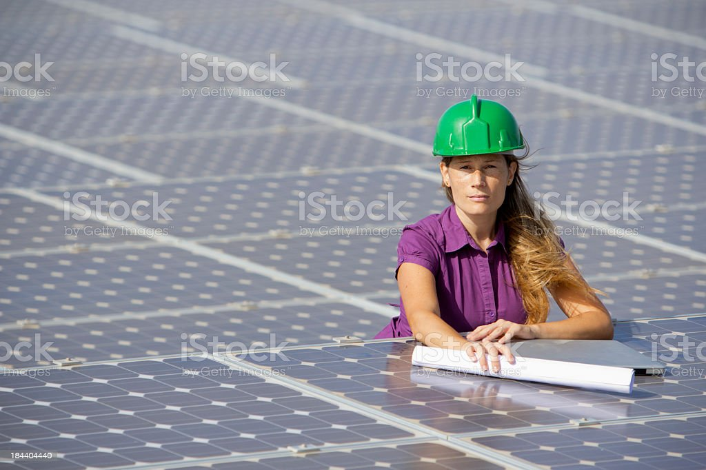 Woman in a purple shirt on top of multiple solar panels royalty-free stock photo