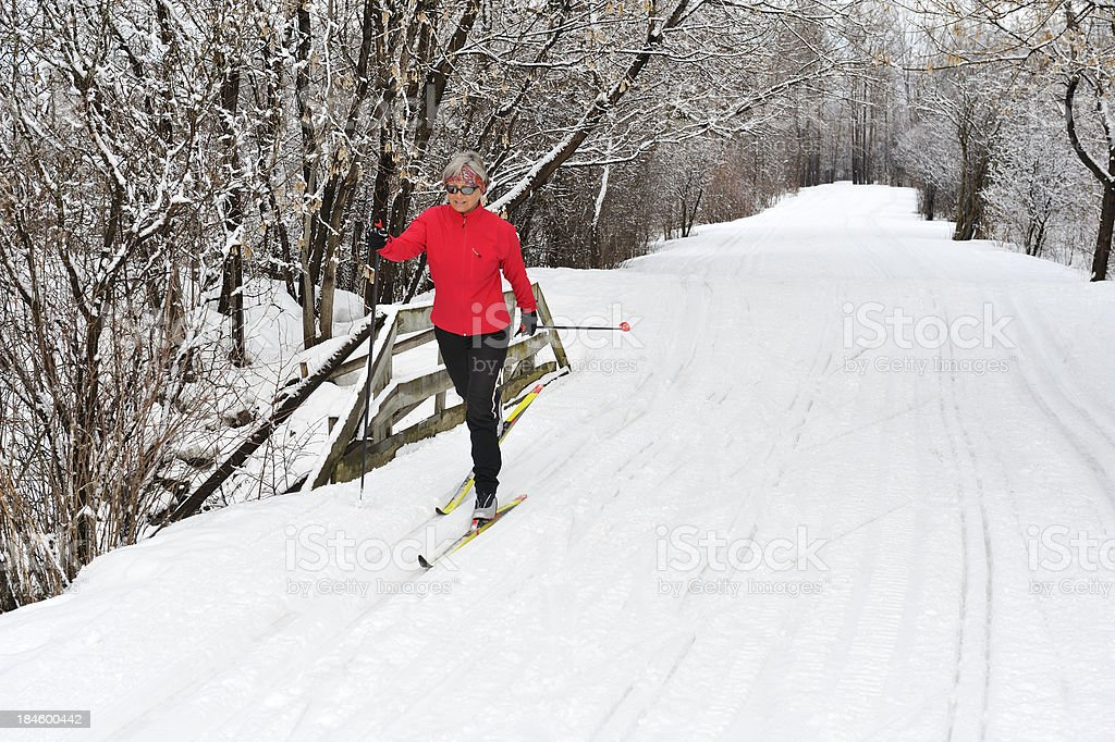 A woman in a red jacket cross-country skiing stock photo
