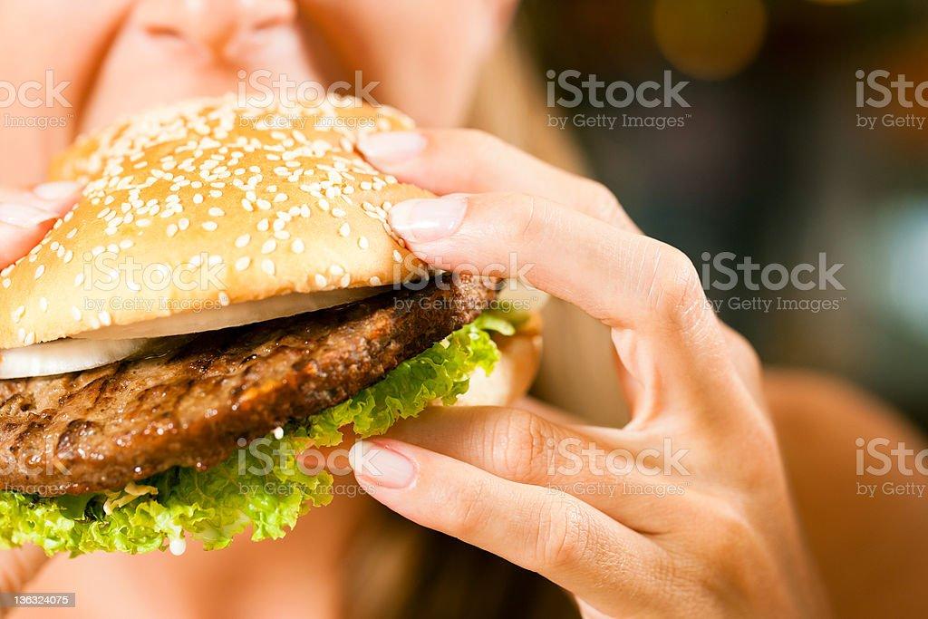 Woman in a restaurant eating hamburger royalty-free stock photo