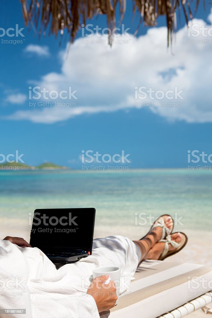 woman in a robe drinking coffee and working on laptop royalty-free stock photo