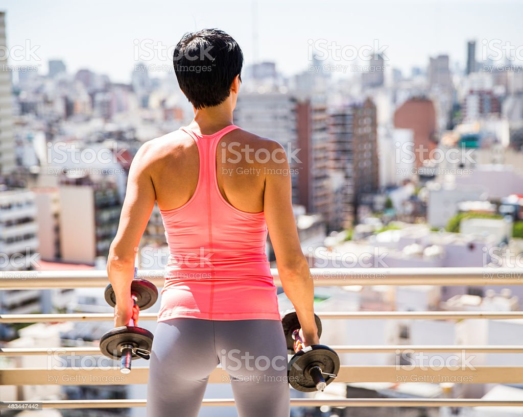 Woman in a rooftop Gym looking at the city stock photo