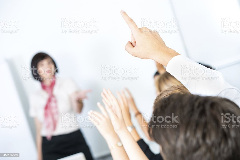 Woman in a scarf teaching a class of eager students royalty-free stock photo