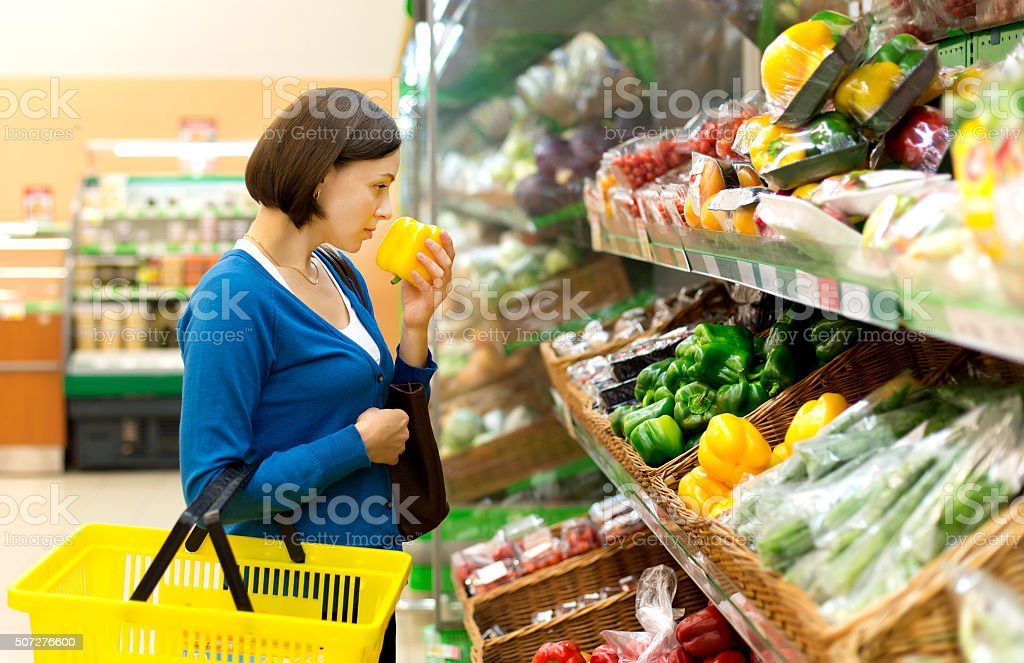 woman in a shop considering vegetables. stock photo