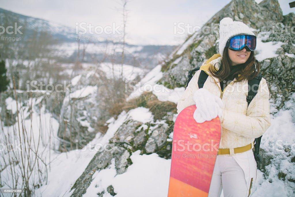 Woman in a ski suit in winter near snowboard stock photo