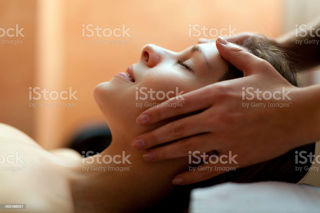 Woman in a spa having her head massaged stock photo