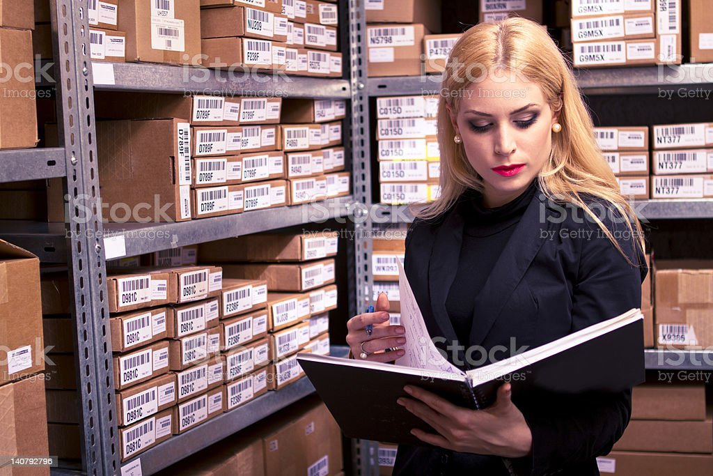 Woman in a storage room reading the pages of a book stock photo
