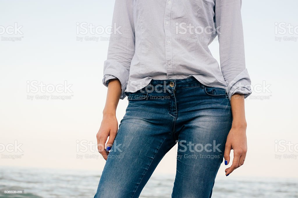 Woman in a striped shirt and blue jeans stock photo