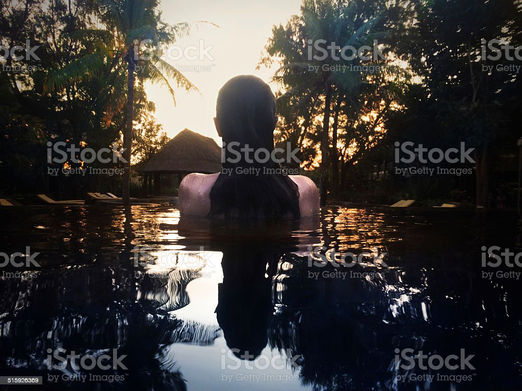 Woman in a tropical pool watching the sunset royalty-free stock photo