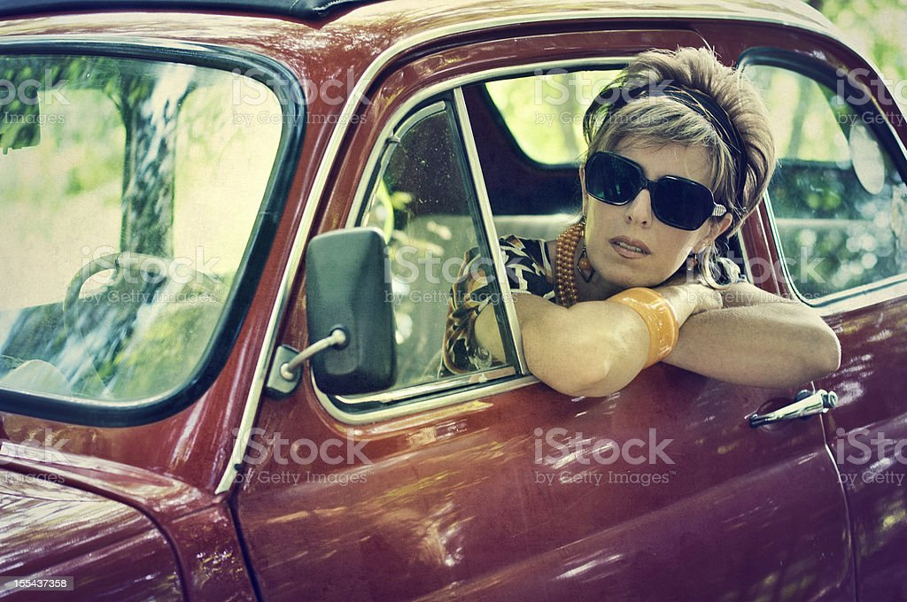 Woman in a vintage italian car. 1970s style. stock photo