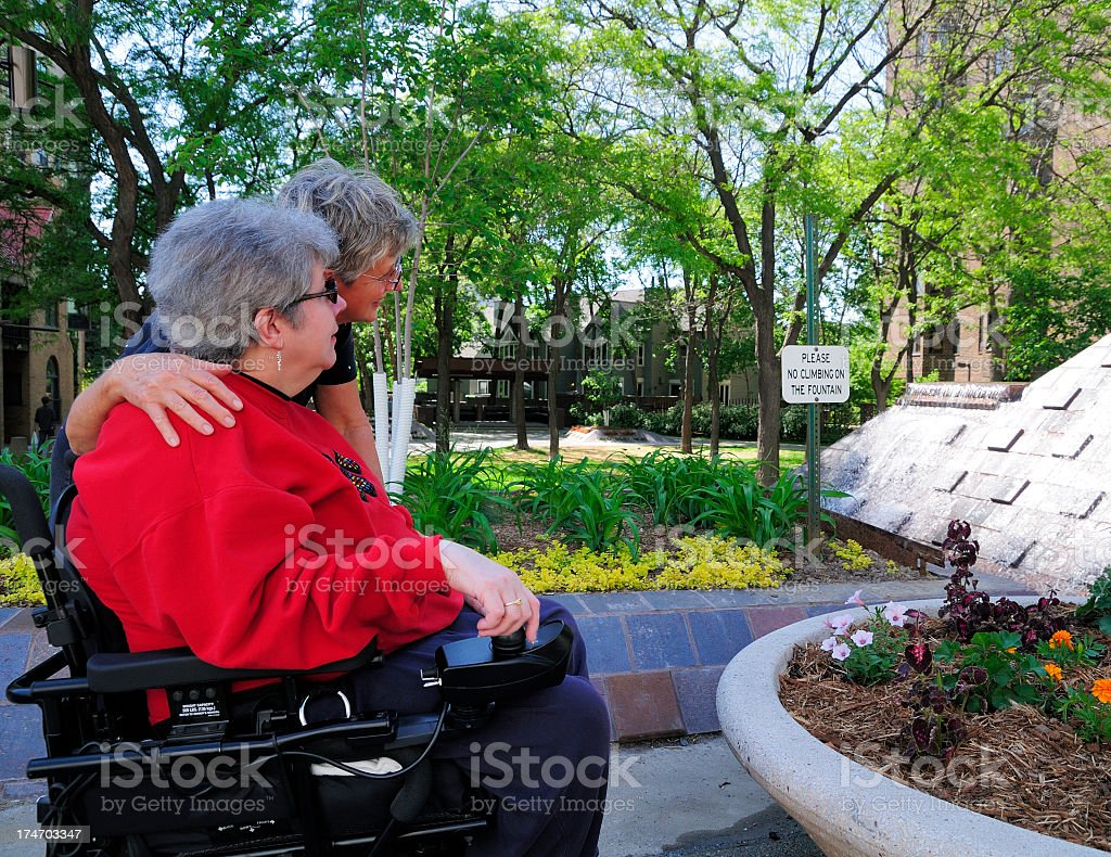 A woman in a wheelchair accompanied by another woman stock photo