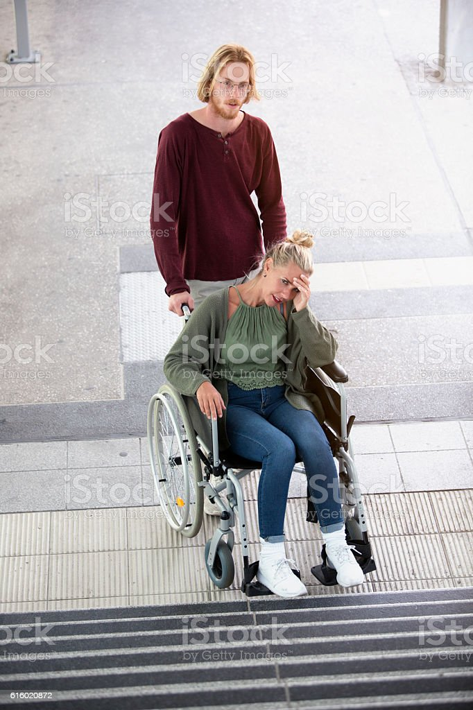woman in a wheelchair in front of stairs stock photo
