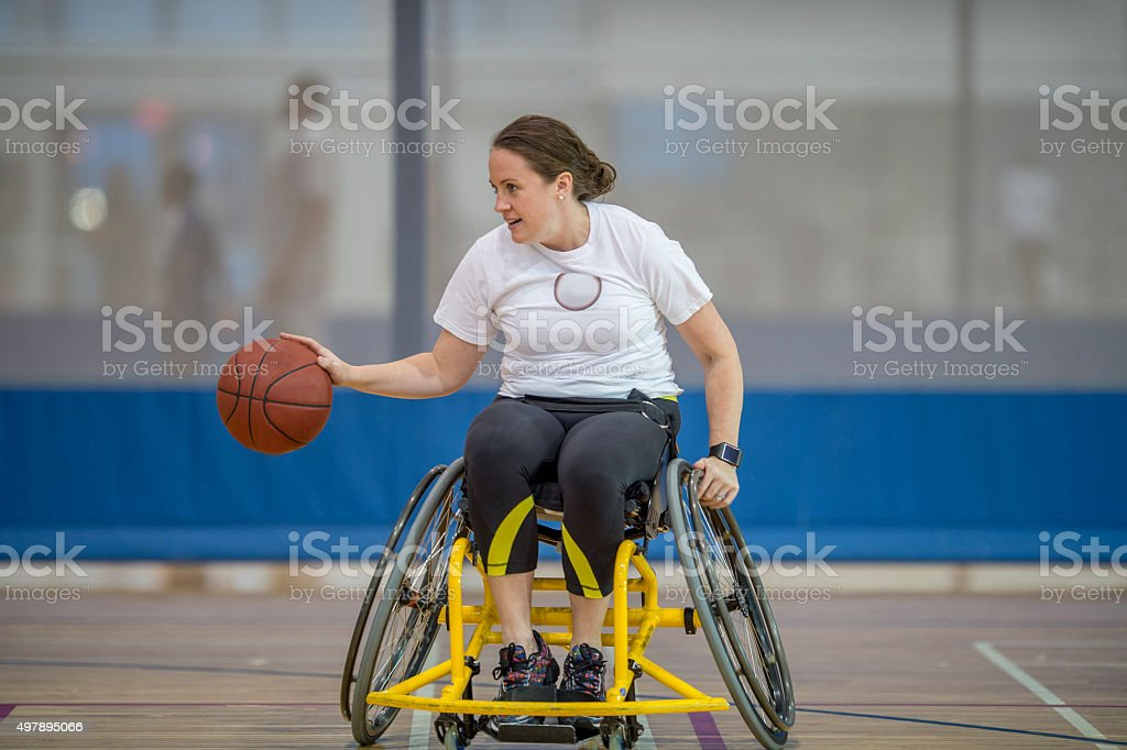 Woman in a Wheelchair Playing Basketball stock photo