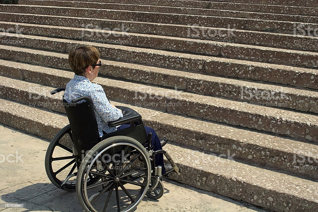 A woman in a wheelchair sitting in front of stairs stock photo