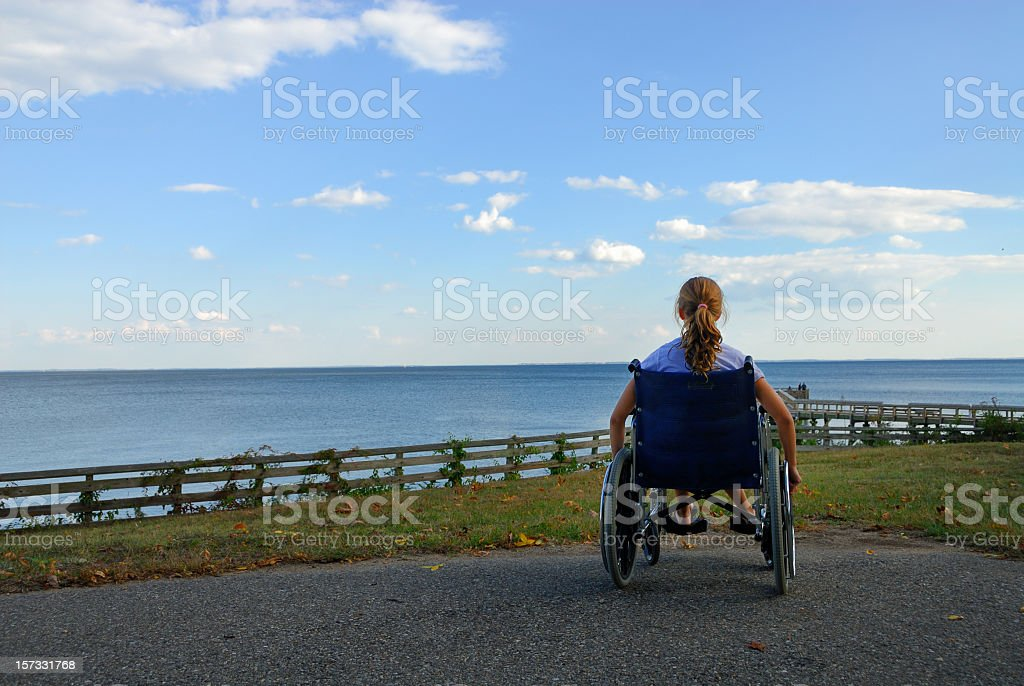 A woman in a whelk chair dreaming she could swim royalty-free stock photo