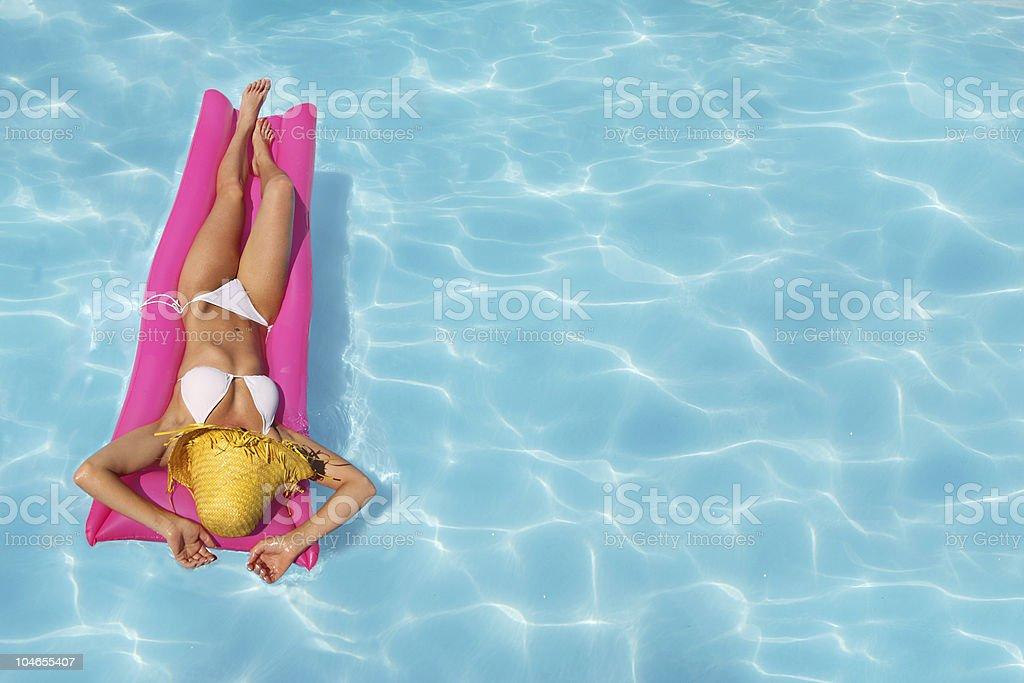 A woman in a white bikini sunbathing in the pool royalty-free stock photo