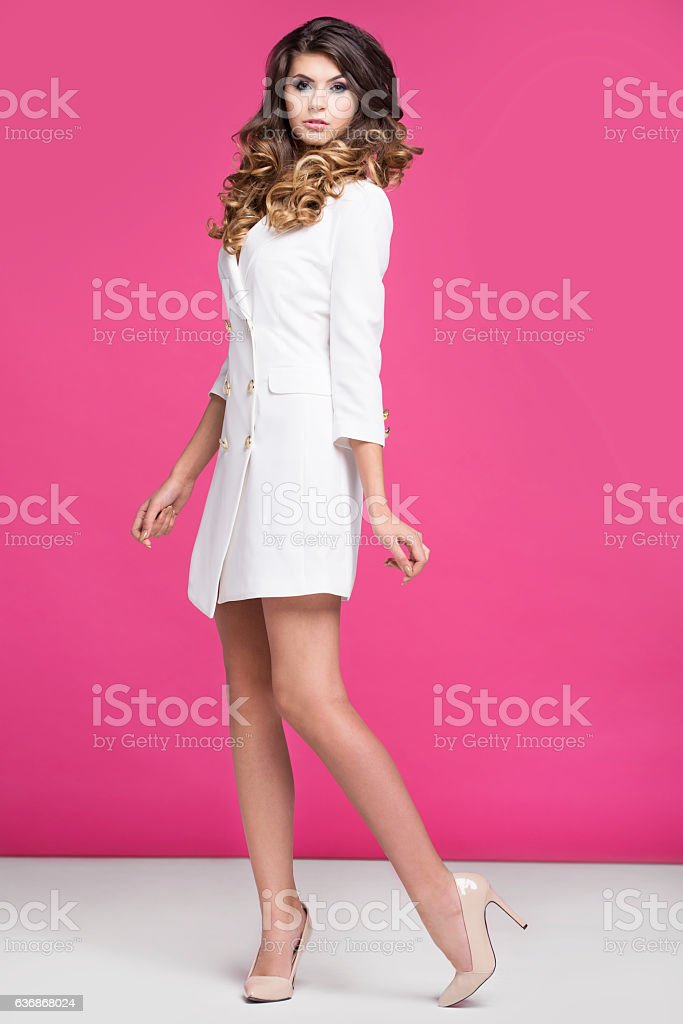 Woman in a white dress standing on a pink background stock photo