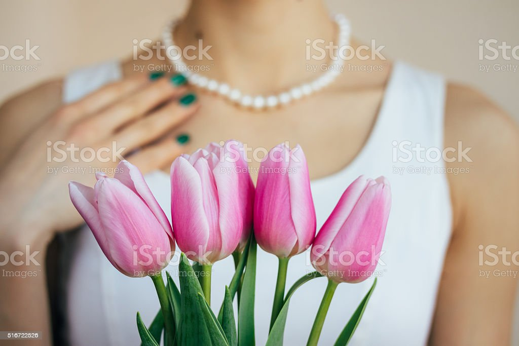 Woman in a white dress takes a gift of tulips stock photo