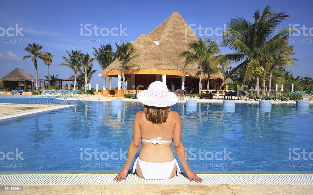 Woman in a white suit putting her feet in the pool royalty-free stock photo