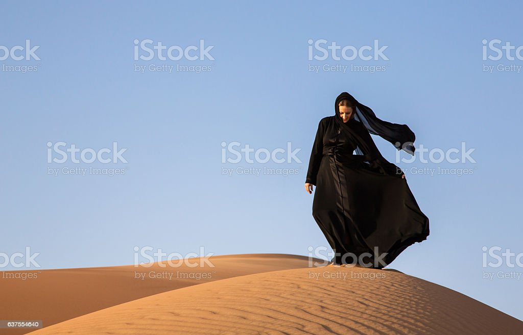 Woman in abaya in sanddunes in Liwa Desert, Aby Dhabi, UAE stock photo