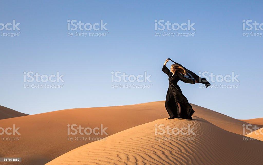 A woman in abaya in sanddunes of Liwa Desert stock photo