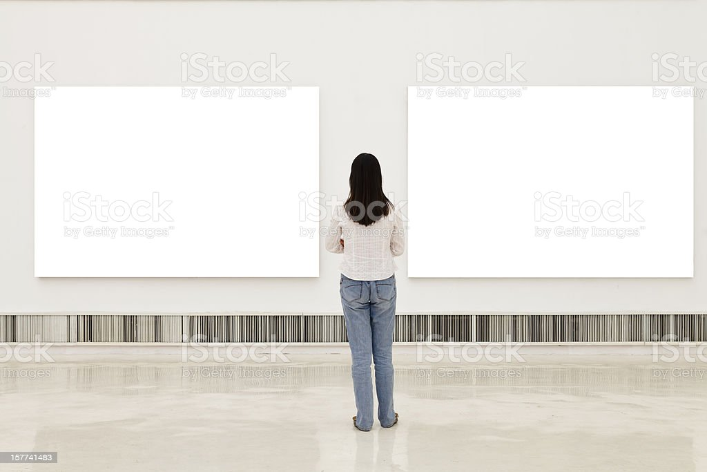 A woman in an art gallery looking at white frames stock photo