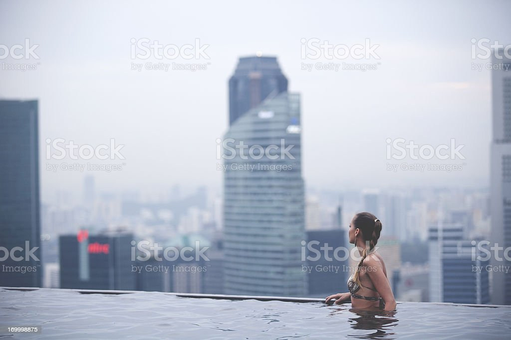 A woman in an infinity swimming pool overlooking the city stock photo