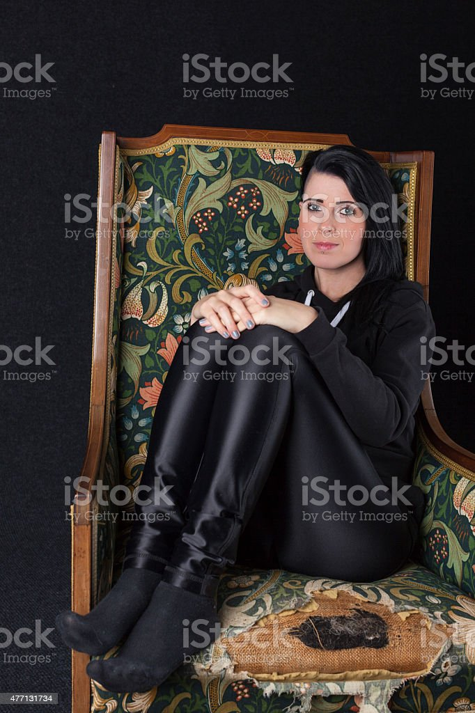 Woman In An Old Armchair stock photo
