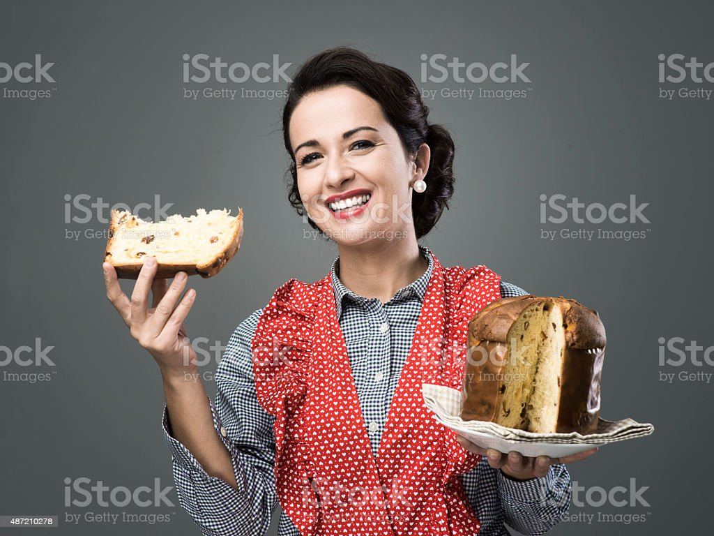 Woman in apron eating panettone stock photo