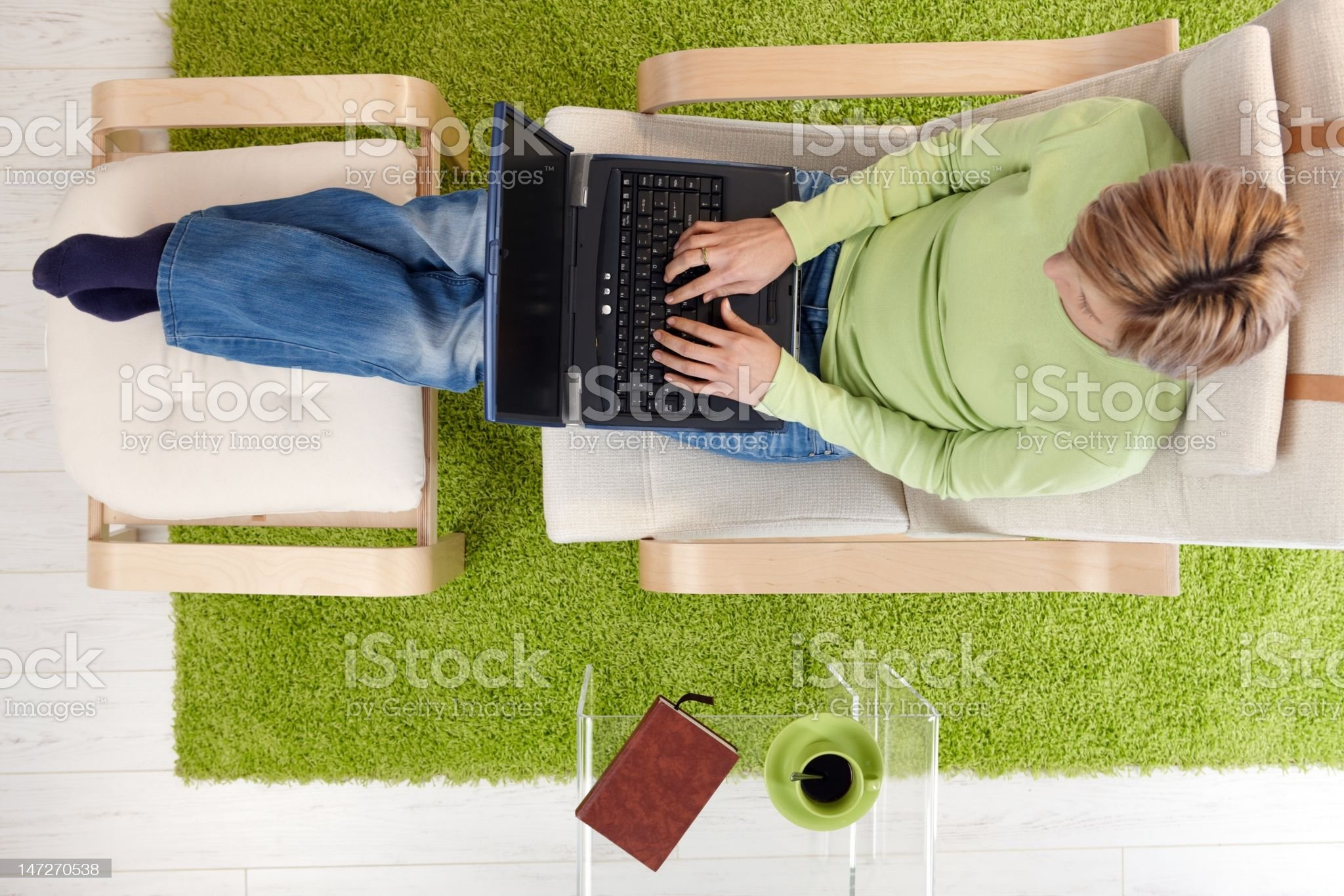 Woman in armchair with laptop royalty-free stock photo