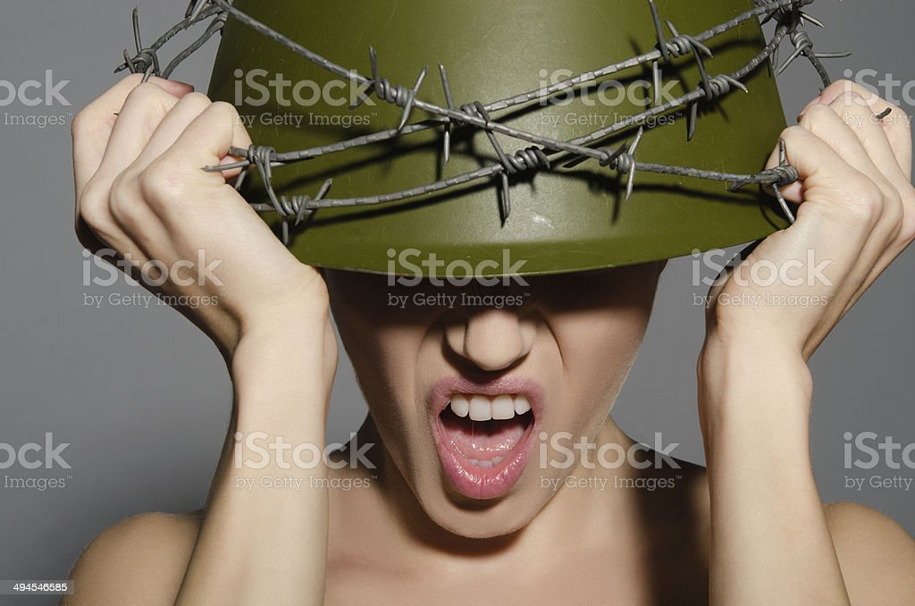 Woman in army helmet with barbed wire stock photo