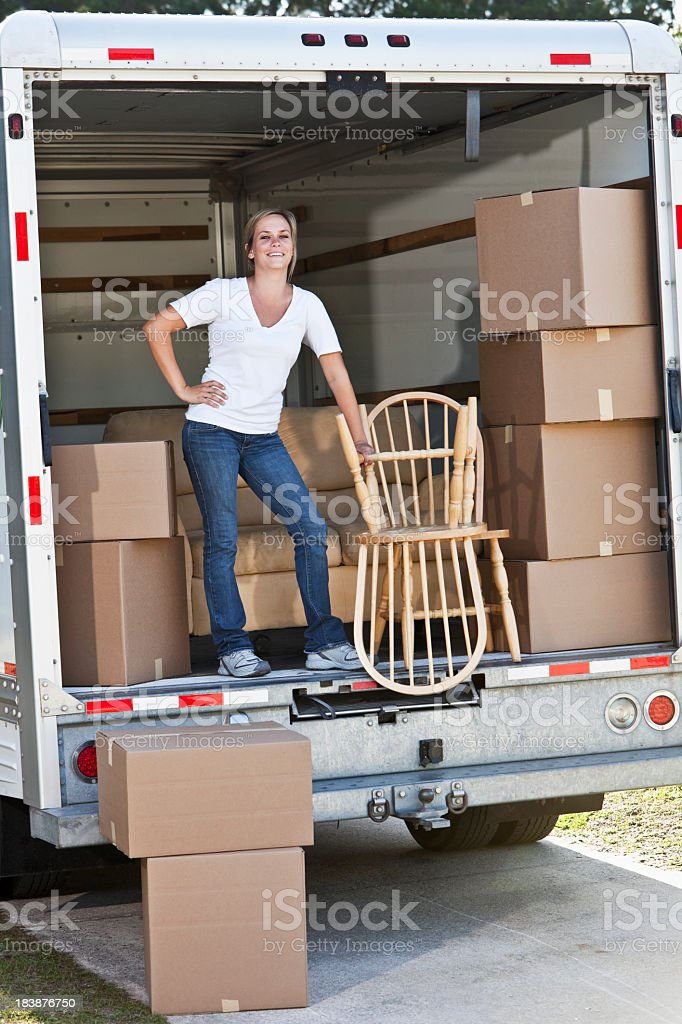 Woman in back of moving van with boxes and furniture stock photo