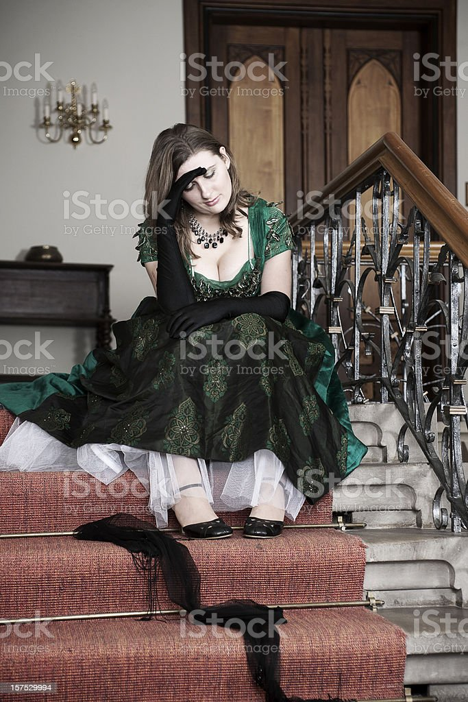 Woman in barock dress sitting on stairs stock photo