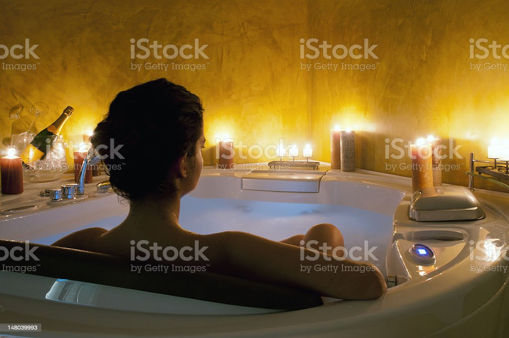 Woman in bath tub with candles stock photo