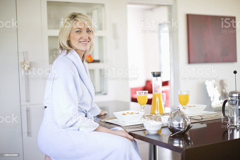 Woman in bathrobe at breakfast table stock photo