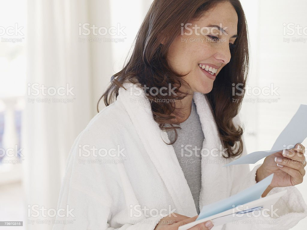 Woman in bathrobe reading a letter royalty-free stock photo