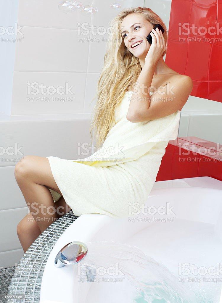 Woman in bathroom speaking on phone royalty-free stock photo