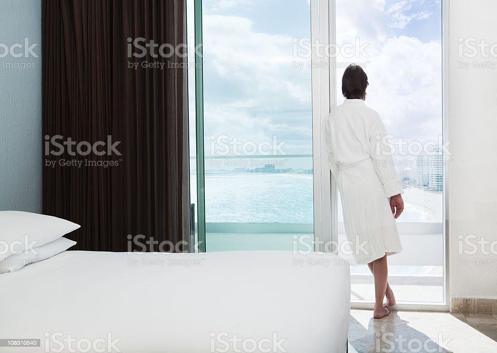 Woman in Beach Resort Hotel Room Relaxing, Admiring Balcony View stock photo
