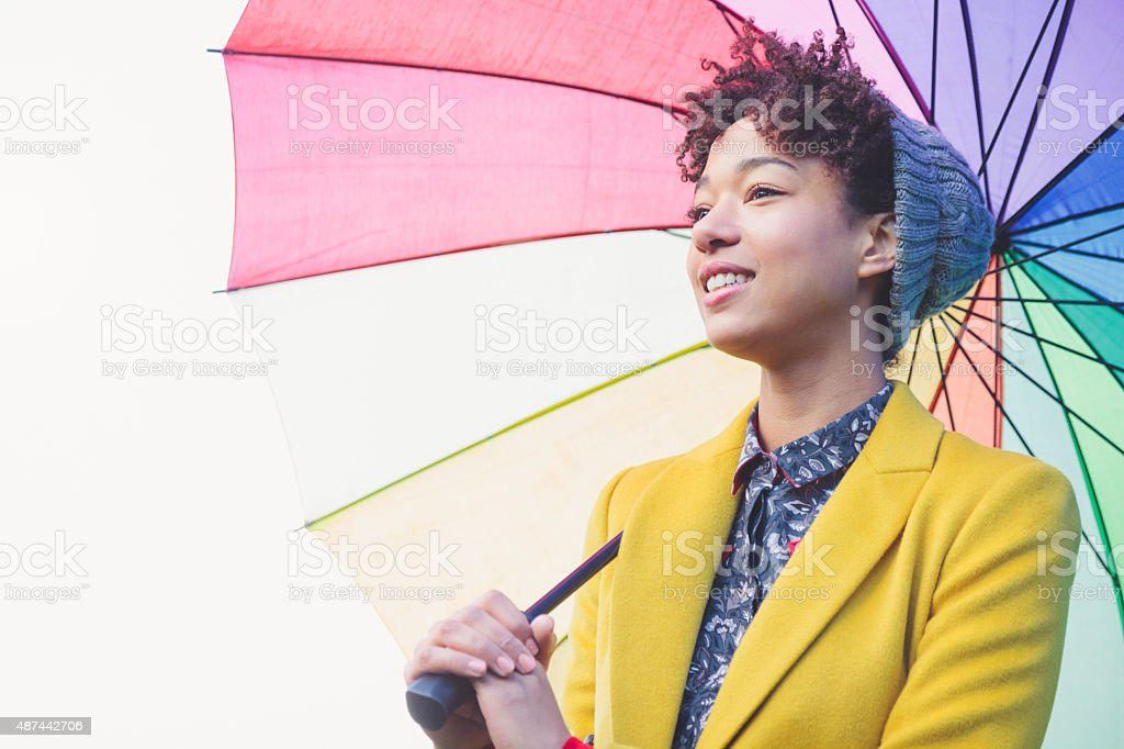 Woman in beanie hat under colorful umbrella (London, UK) stock photo