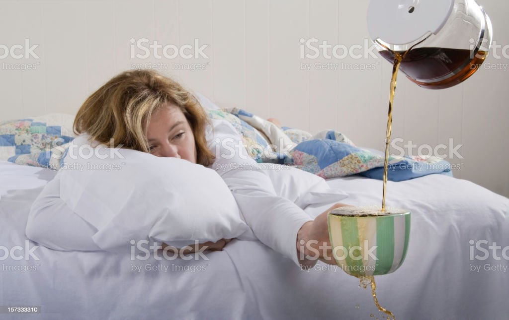 A woman in bed holding an overflowing coffee mug in her hand stock photo