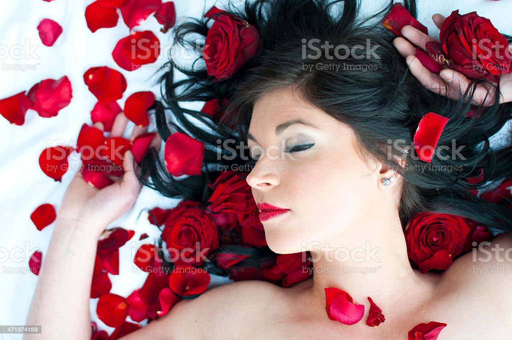 Woman in bed of roses stock photo