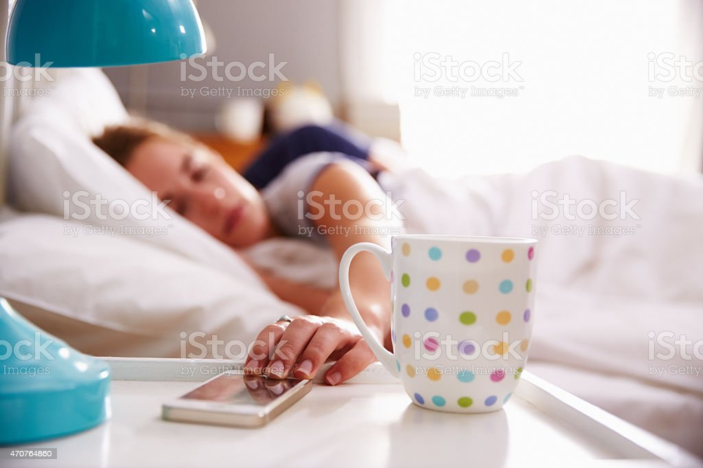 Woman in bed reaching for her mobile phone on nightstand stock photo