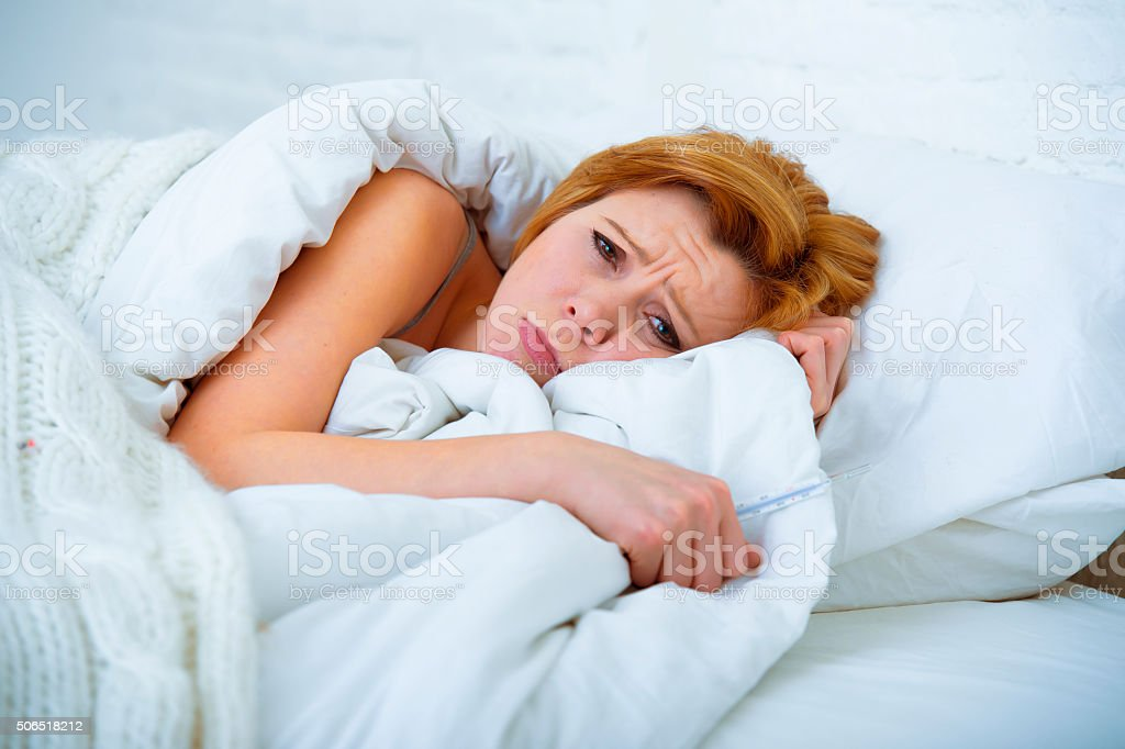 woman in bed sick unable to sleep suffering depression stock photo